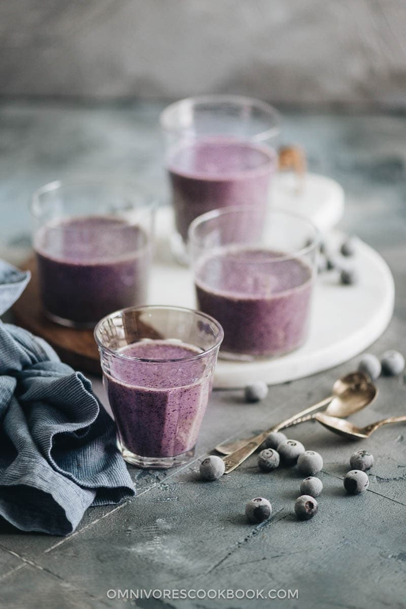 Blueberry banana smoothie with frozen blueberries garnish