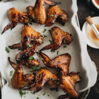 Baked honey soy chicken wings on parchment lined baking sheet