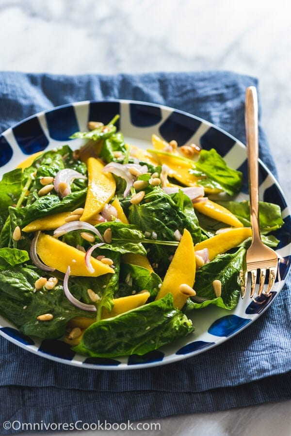 The spinach salad is served with a refreshing sweet and sour vinaigrette with sweet mango slices and toasted pine nuts. It takes no time to put together and adds a delicious green to your main dish!