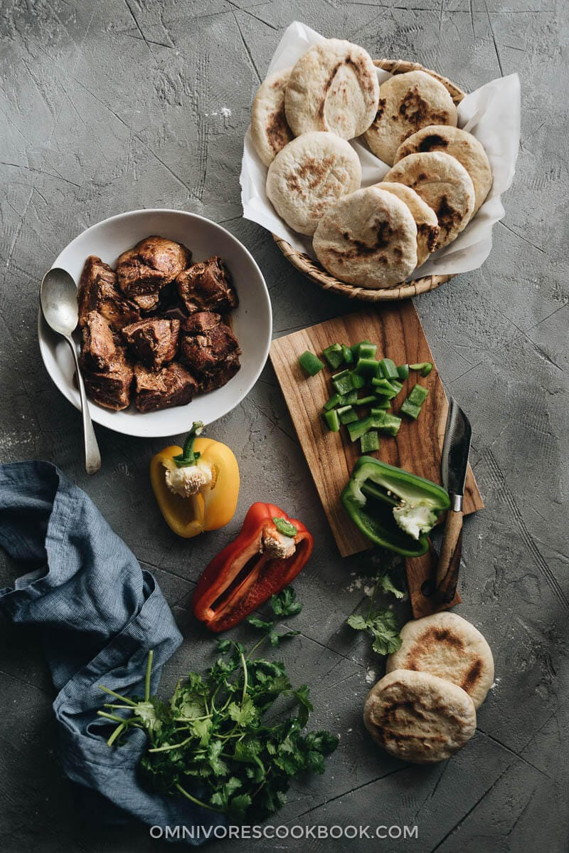 Flatbreads, braised pork belly, and chopped pepper and cilantro for making pork belly buns