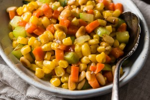 Stir Fried Corn with Pine Nuts (松仁玉米) - The sweet corn kernels, pine nuts, cucumber, and carrot are lightly seasoned with green onion, salt, and sugar. Every ingredient comes together to create a hearty meal that is nutty and sweet | omnivorescookbook.com