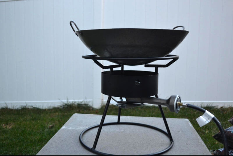 Carbon steel wok on an outdoor high output gas range.