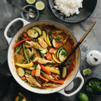 Vegetarian Thai curry in dutch oven with a plate of rice on the side