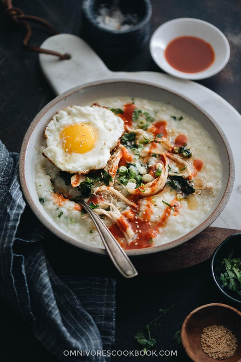 Instant Pot congee with chicken and spinach topped with egg served in a bowl