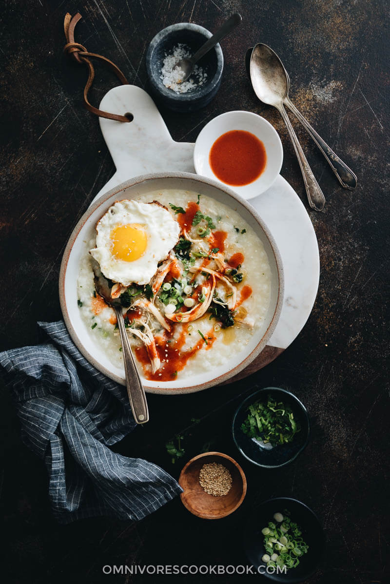Instant Pot congee with chicken and spinach topped with egg served in a bowl with sauce and toppings on the side