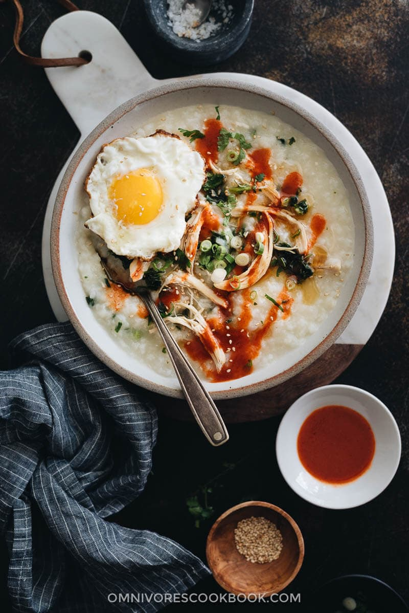 Close up of Instant Pot congee with chicken and spinach topped with egg served in a bowl