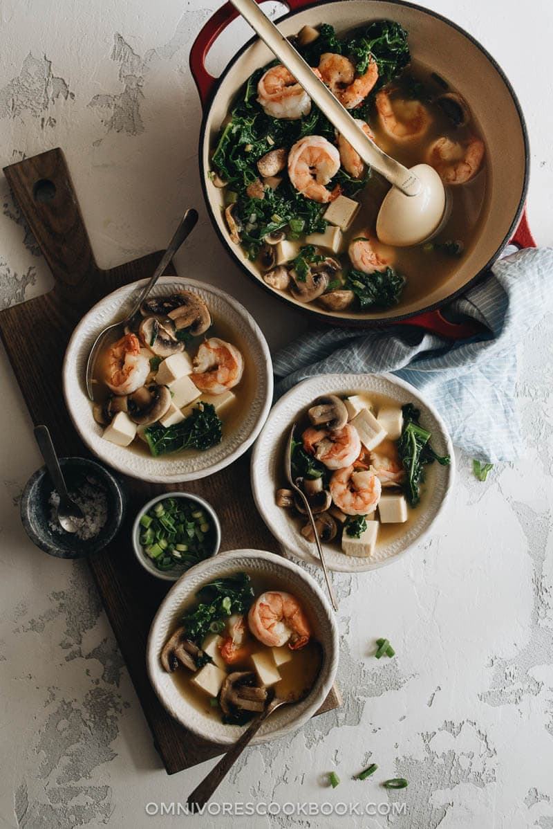 A big pot and three small bowls of shrimp soup with tofu and kale