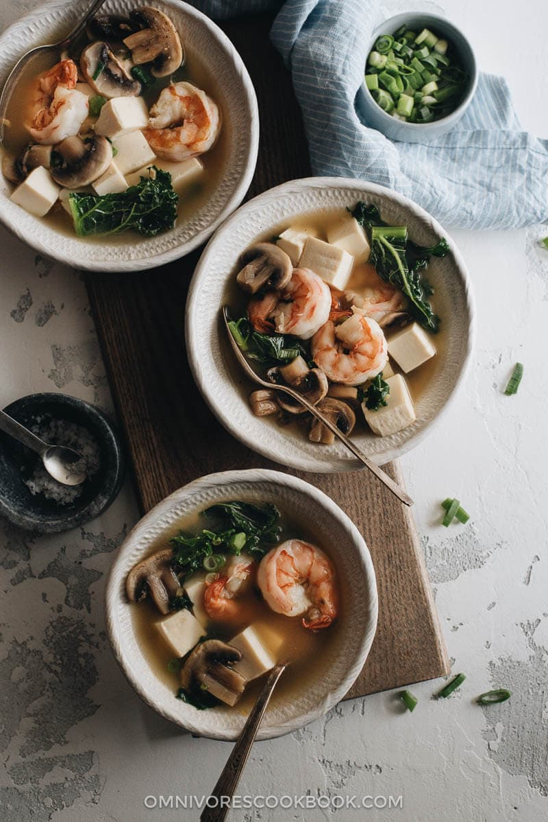 Three small bowls of shrimp soup with tofu and kale