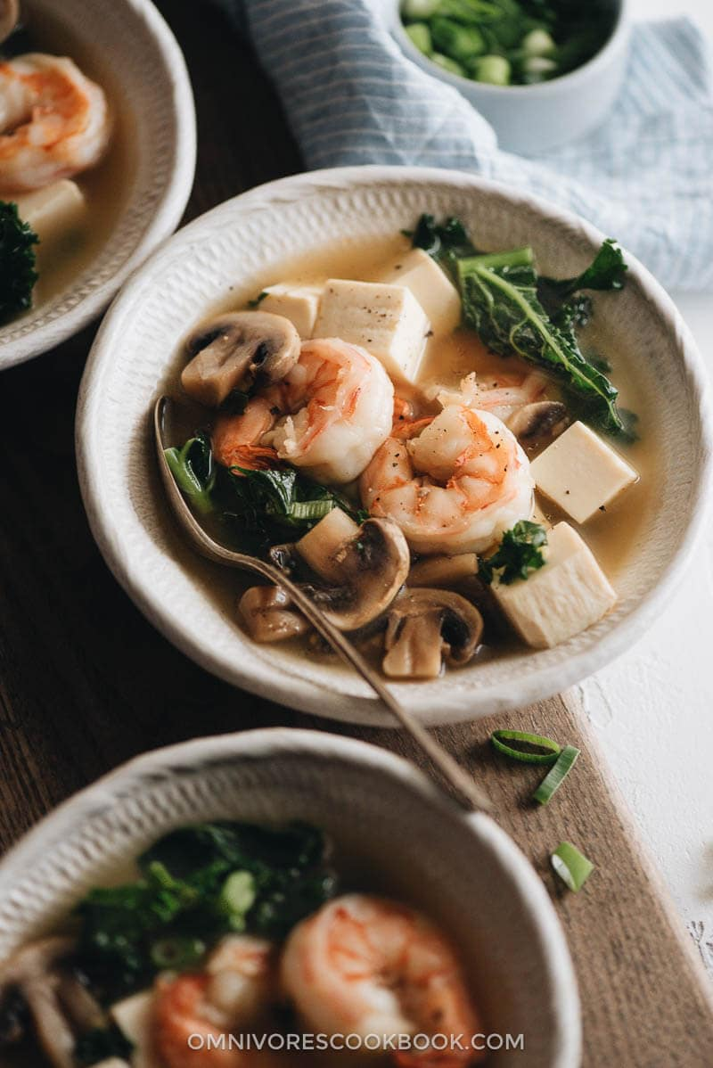 Closeup of a bowl of shrimp soup with tofu and kale