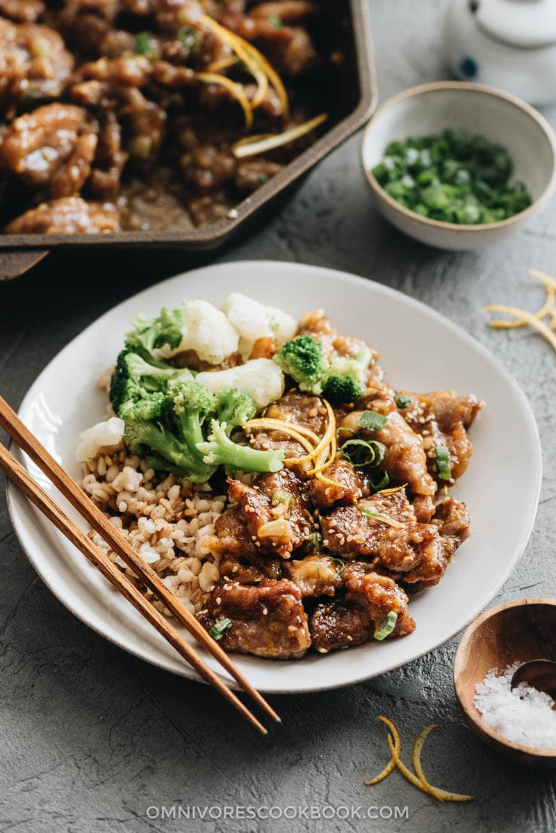 Orange beef served in a plate with rice, cauliflowers and broccoli