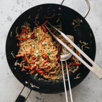 Garlic noodles cooked in a wok with spatula and a pair of tongs