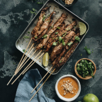 Beef satay served with peanut sauce and cilantro