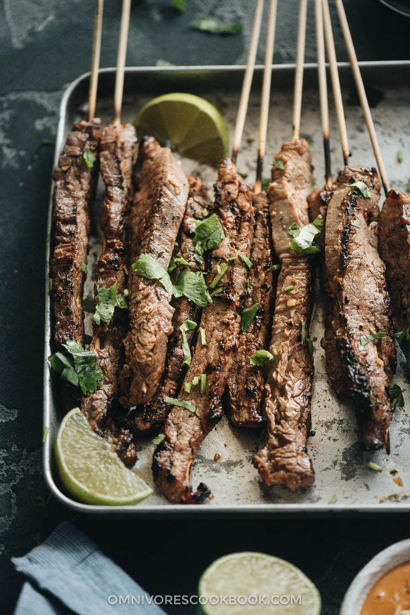 Beef satay served with peanut sauce and cilantro close up