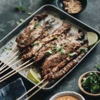 Beef Satay - Skewers of flavorful beef get that perfect char over the Chinese grill and are served with a sweet, tangy and totally craveable peanut sauce. #marinade #recipe #sticks #gluten-free