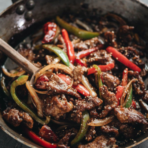 Easy Szechuan Beef Stir Fry - Tender crispy beef cooked in a bold sweet sour spicy sauce with peppers and onions. Learn how to make the richest sauce and create crispy beef without deep-frying. {Gluten-free adaptable}