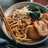 Hokkien Prawn Mee Noodle Soup (Hae Mee) - Tender yellow noodles in a rich savory-sweet red-orange broth served with juicy prawns, fish cakes, crunchy bean sprouts, and crispy fried shallots. {Gluten-Free adaptable}