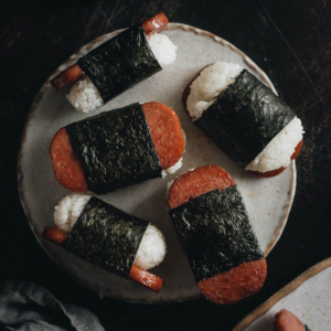 Spam Musubi - The spam is grilled until crispy, perfectly caramelized with soy sauce and sugar, and wrapped with sushi rice. Made ahead of time, these Spam musubi are perfect for your lunchbox, appetizer platter, or potluck. They are also a fantastic game-day snack. This recipe uses just the right amount of seasoning to create a balanced flavor that's addictively tasty.