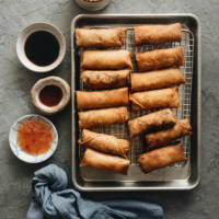 Fried Chinese egg rolls on cooling rack