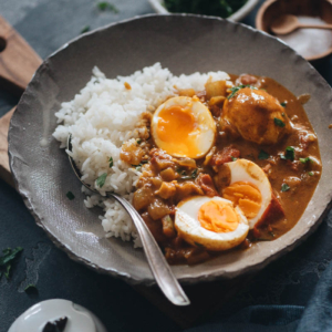 Egg curry served with steamed rice in a bowl