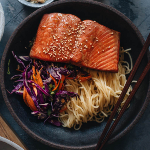 30-Minute Salmon Noodle Bowl with Coleslaw - Tender flaky juicy baked salmon served on noodles with coleslaw in a garlicky gingery savory sauce that's lightly sweet. This recipe uses a blender to mix one sauce that is used as the salmon marinade and in the noodle sauce, so it literally takes 10 minutes to get ready. It's a perfect dish for your busy weekday dinners and meal-prep. {Gluten-Free Adaptable}