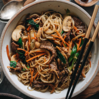 Japchae (Korean Sweet Potato Noodles) | Make japchae at home for a comforting, delicious, and nutritionally balanced weekday dinner. The tender sweet potato noodles are tossed with charred beef and crispy veggies in a sweet savory sauce. This easy recipe uses shortcuts to make the cooking process faster than the traditional recipe. {Gluten Free adaptable, vegan adaptable}