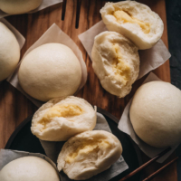 Chinese Steamed Custard Buns (nai wong bao, 奶黄包) | A dim sum classic, these buns are perfect for holiday gatherings and parties as well. Made with a yeast dough and steamed, the buns have a super soft and spongy texture with a smooth surface. The custard filling is creamy, fragrant, and sweet. The recipe includes detailed step-by-step pictures to help you recreate the restaurant-style custard buns in your own kitchen.