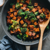Tofu with broccoli in brown sauce in frying pan