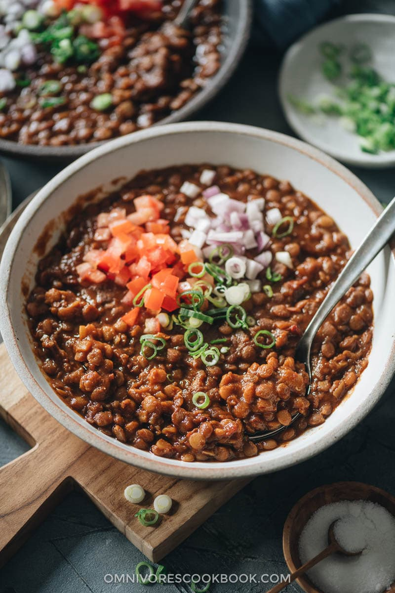 Lentil stew topped with chopped tomato and onion