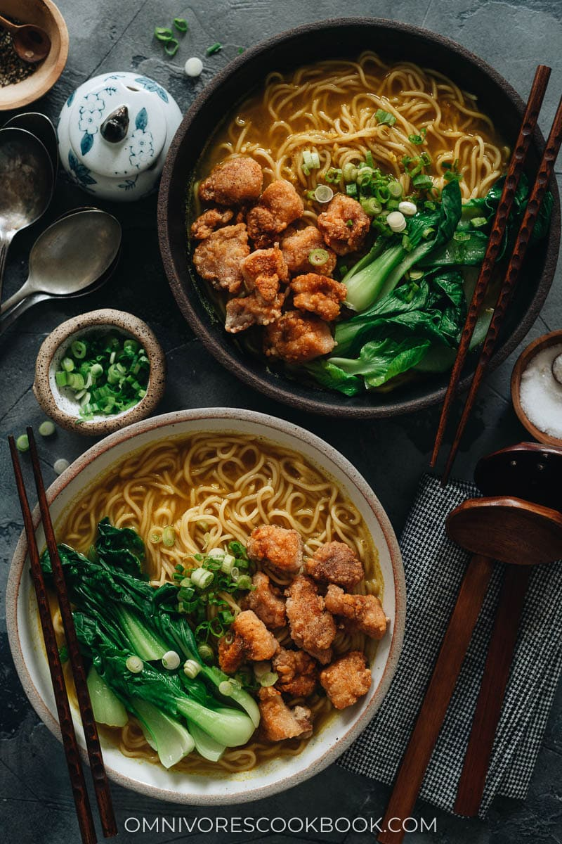 Curry noodle soup topped with popcorn chicken and baby bok choy