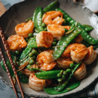 Juicy, tender shrimp with crispy snow peas in a refreshing and healthy gingery sauce. It's a comforting Chinese takeout dish you can whip up quickly any night of the week! {Gluten-Free Adaptable}