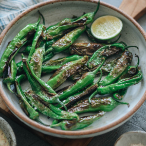 Charred shishito peppers in a bowl