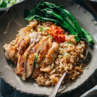 Carved chicken served on rice with Chinese broccoli