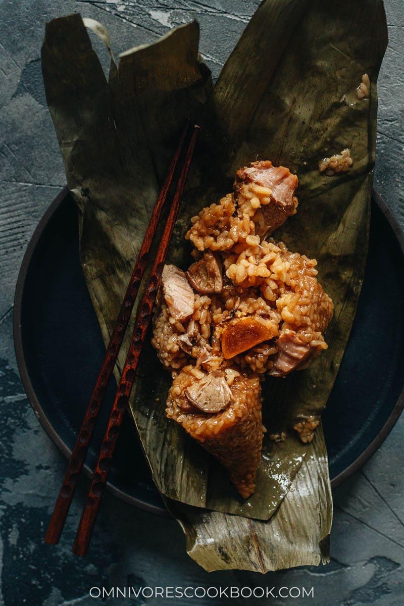 Pulled apart zongzi showing salty duck egg yolk, mushroom, and pork