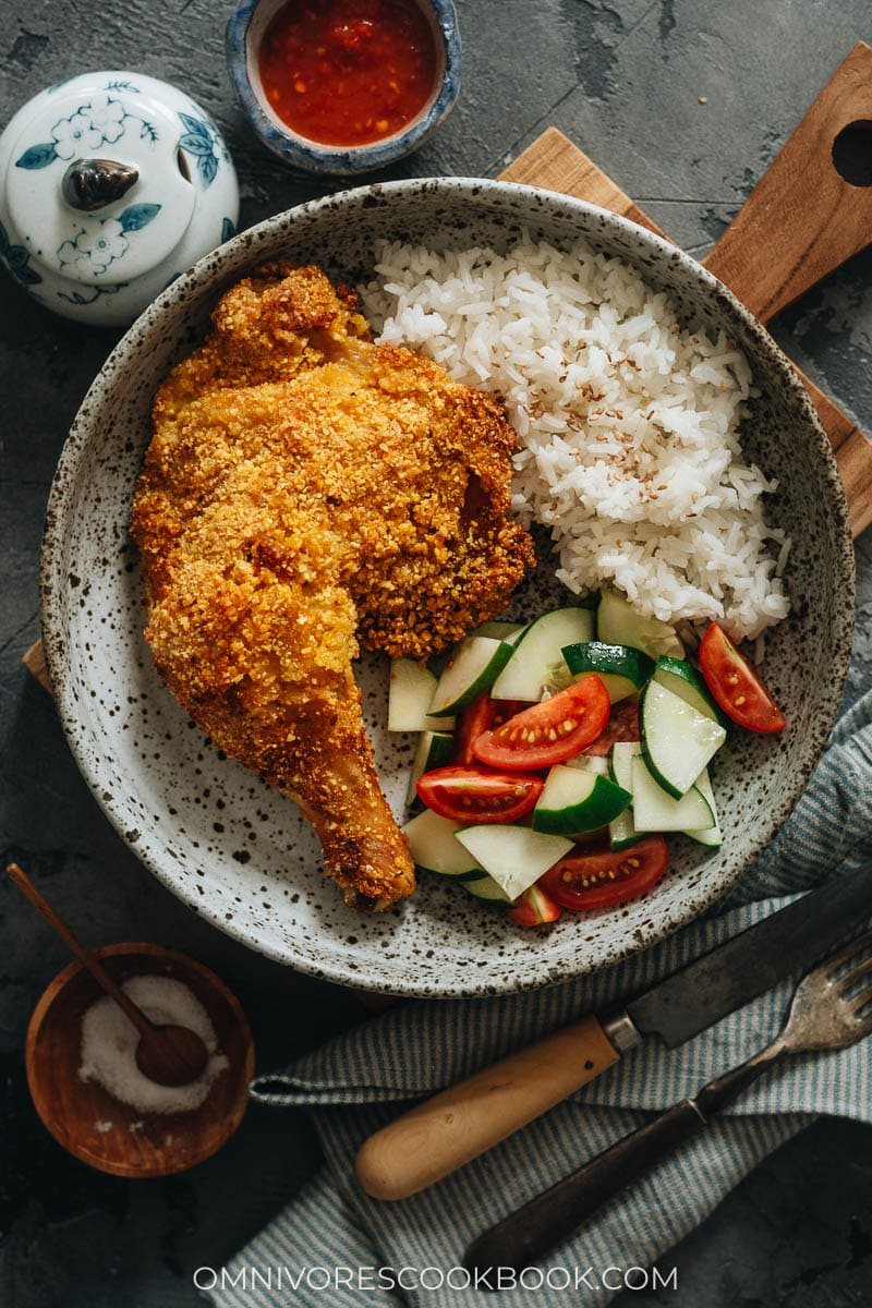 Oven fried chicken leg served with rice and salad