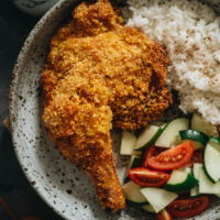Crispy baked chicken leg served with rice and salad