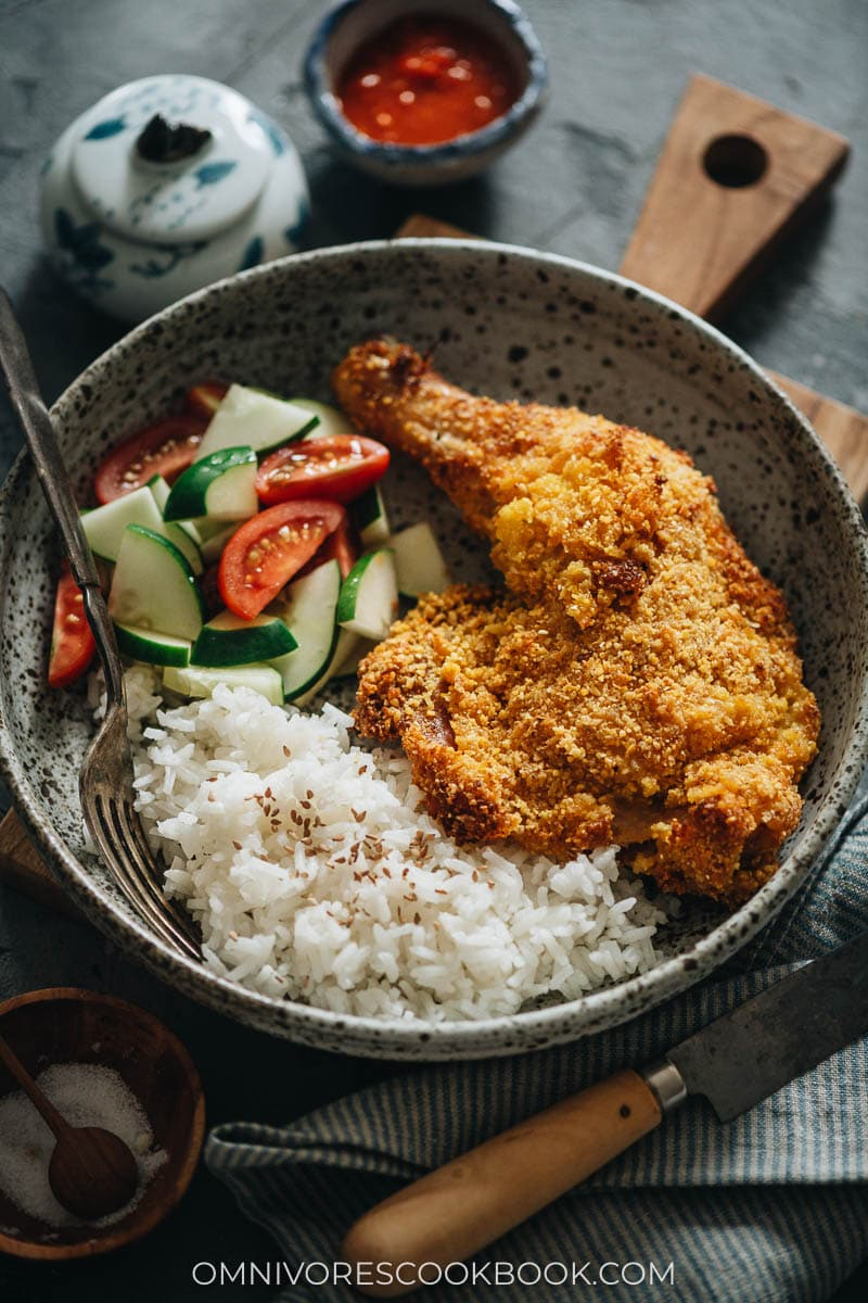 Crispy fried chicken leg served with rice and salad