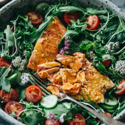 Flaked salmon on arugula with tomato and cucumber