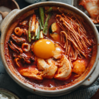 Take your taste buds to Korea with sundubu-jjigae, a delightfully spicy tofu stew that will bring you comfort and warmth in every bowl!