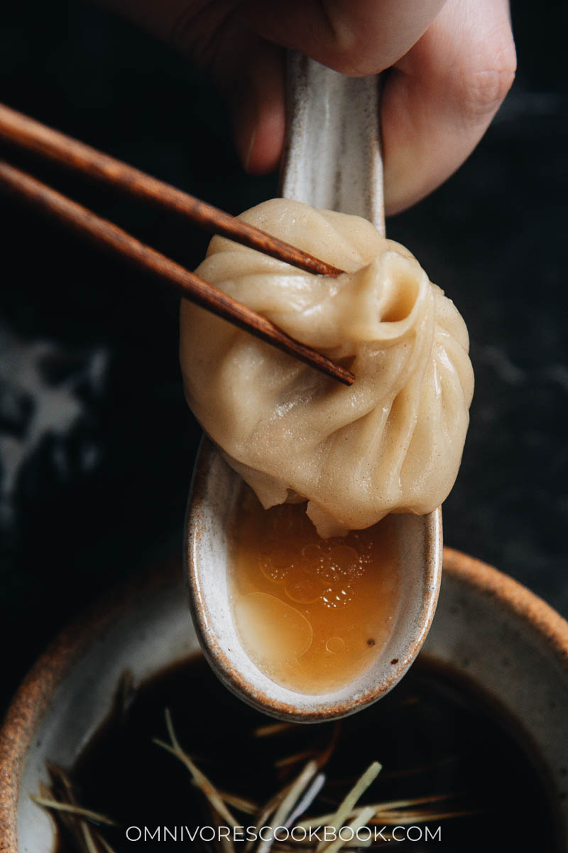 Eating soup dumplings with soup in the spoon