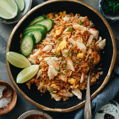 Crab fried rice with lime wedges and cucumber