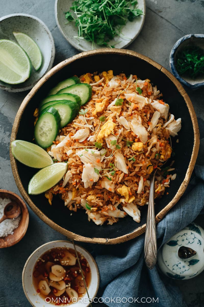 Crab rice with lime wedges and cucumber