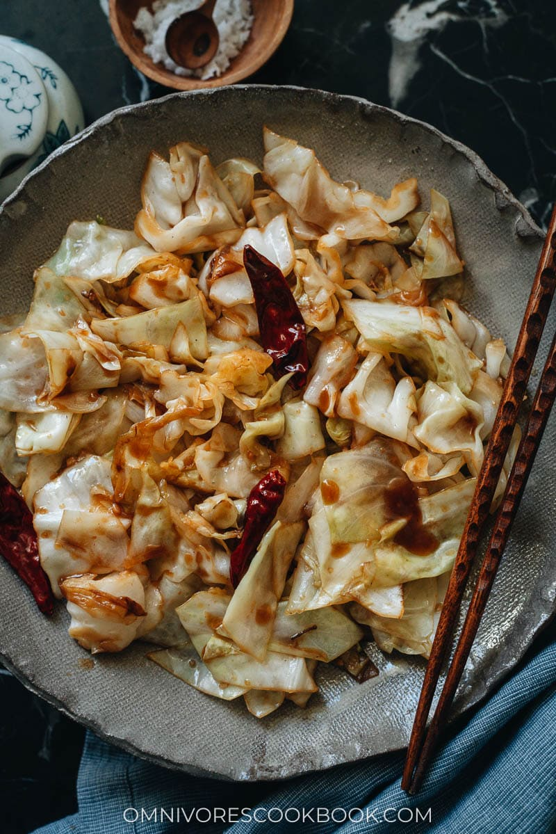 A bowl of sauteed cabbage with chile peppers and chopsticks