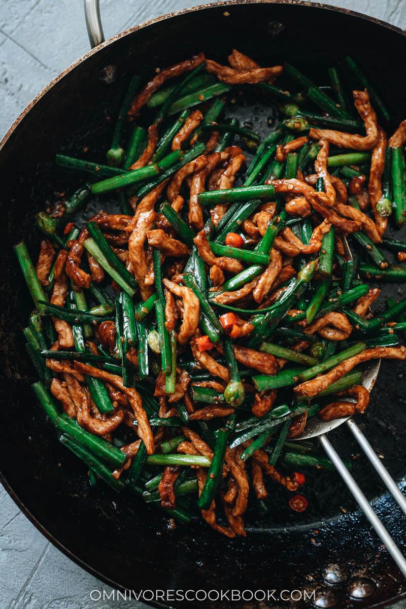 A skillet full of stir fried pork with garlic chives
