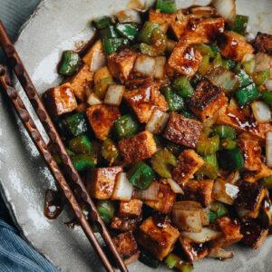 Close-up of crispy stir-fried tofu, green pepper, celery, and onion