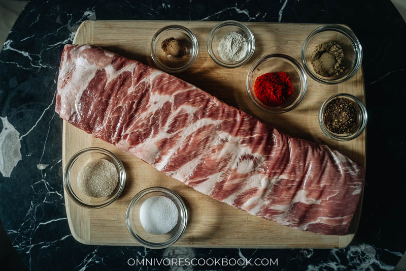 A raw rack of pork ribs with spices for rubbing