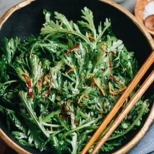 Chrysanthemum greens in a bowl with Asian dressing