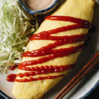 Kimchi fried rice omelet with tomato ketchup and cabbage salad