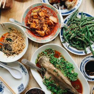 A Sichuan Chinese dinner spread with whole fish, mapo tofu, green beans, and eggplant