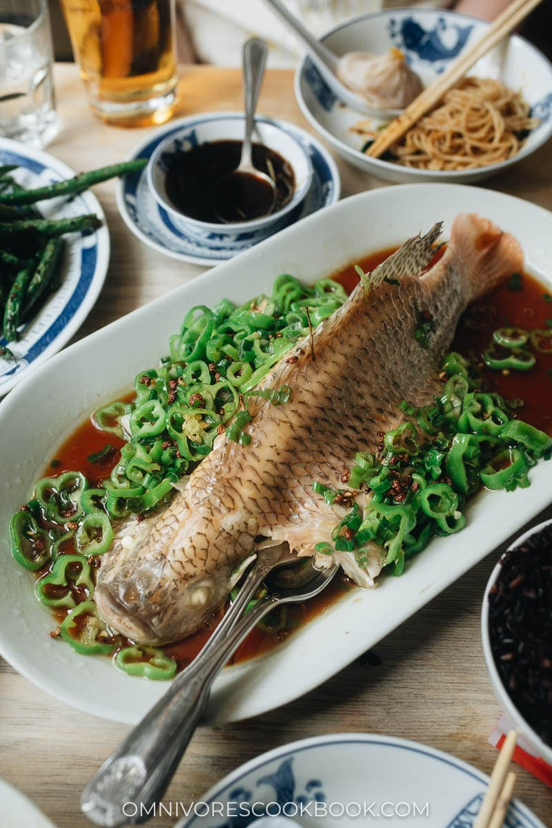 Whole steamed fish on a plate with chile peppers and soy sauce at Birds of a Feather