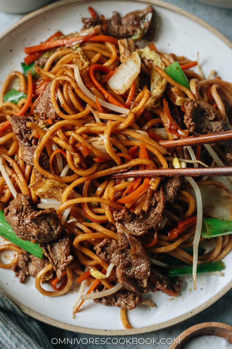 Closeup of chopsticks grabbing a bite of beef lo mein